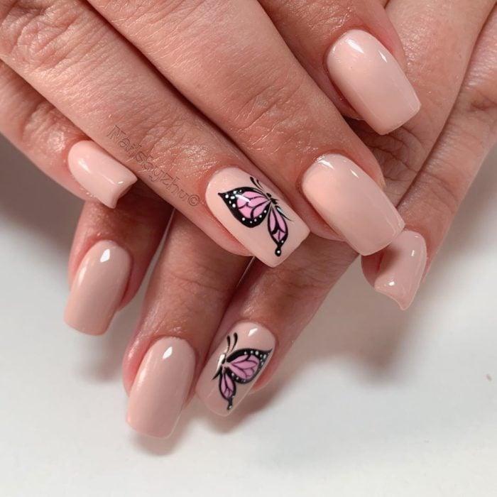 Chica con unas uñas de mariposa en colores nude con negro