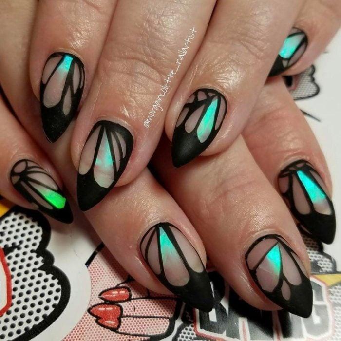 Chica con unas uñas de mariposa en colores negro con azul y verde