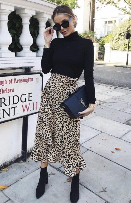 Chica usando una falda animal print, blusa, bolso y botines en color negro