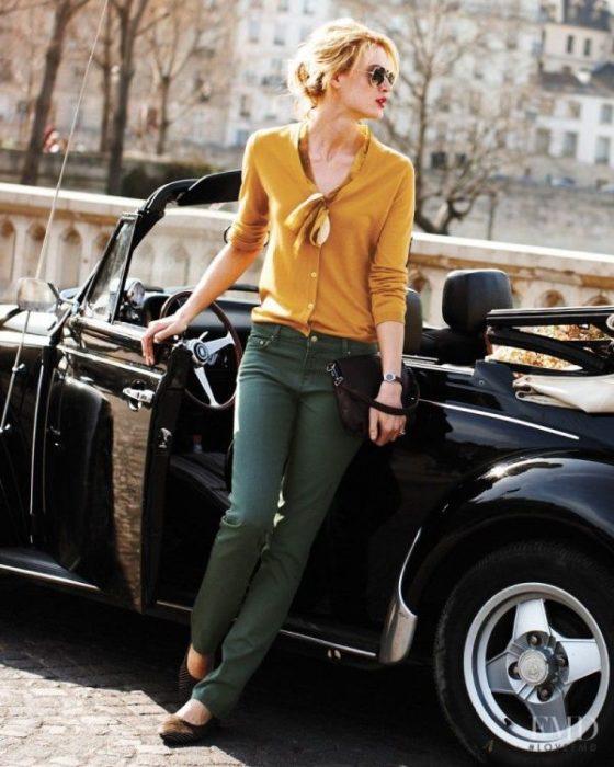 Chica bajando de un auto mientras muestra su outfit de pantalón verde y blusa color mostaza