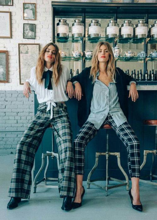 Chicas sentadas en un bar mientras posan en una sesión de fotos