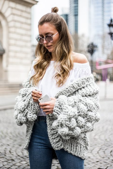 Chica caminando por la calle y usando un abrigo de lana tejido, jeans y blusa campesina de color blanco