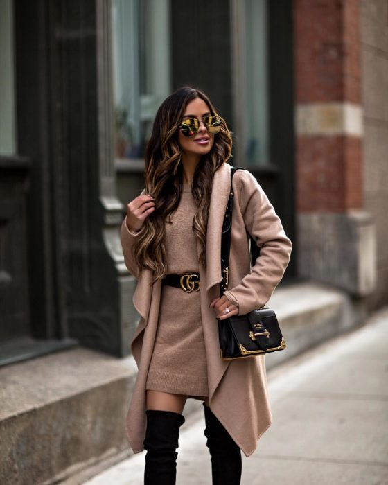 Chica usando un vestido y abrigo en color café con un cinturón chanel y botas mientras camina por la calle