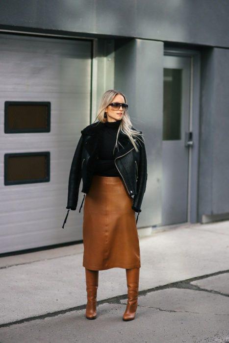 Chica usando una falda de cuero color café y botas, con chamarra de cuero y suéter negro