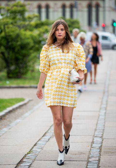 Chica usando unas botas de color blanco con negro y un vestido amarillo mientras camina por las calles