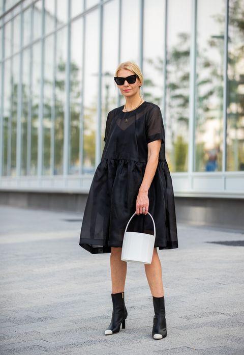 Chica usando un vestido de color negro con unos botines de color negro con punta blanca
