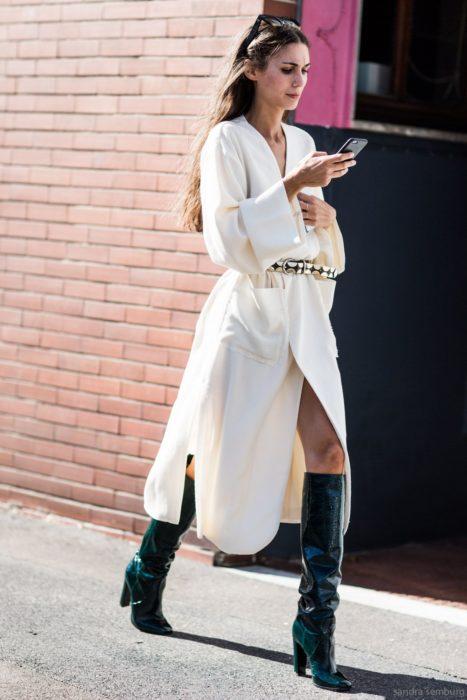 Chica usando un vestido blanco y botas de charol verde mientras camina por la calle mirando su celular