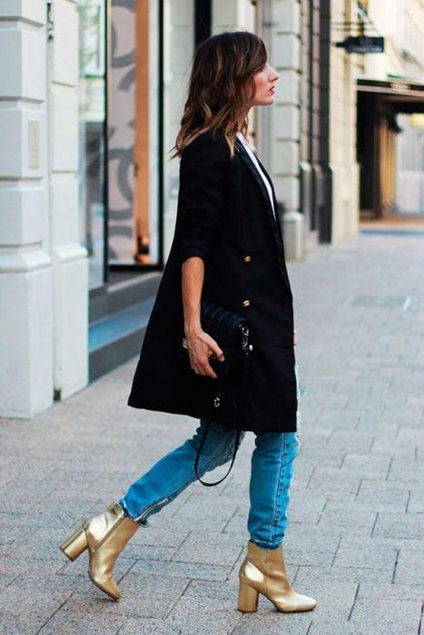 Chica caminando por la calle mientras usa unos botines de color dorado
