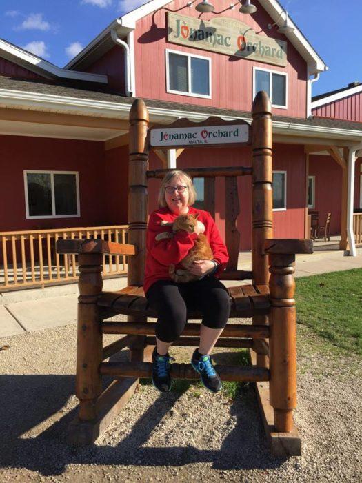 Melissa Blake sentada en una gran mecedora de madera afuera de una casa de madera