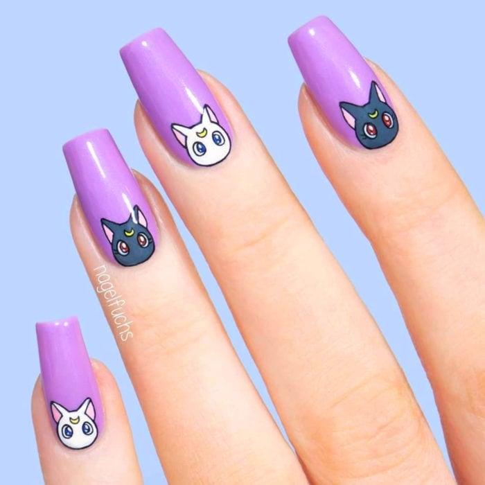 Manicura de Sailor Moon; uñas largas cuadradas pintadas de morado con gatos Luna y Artemis