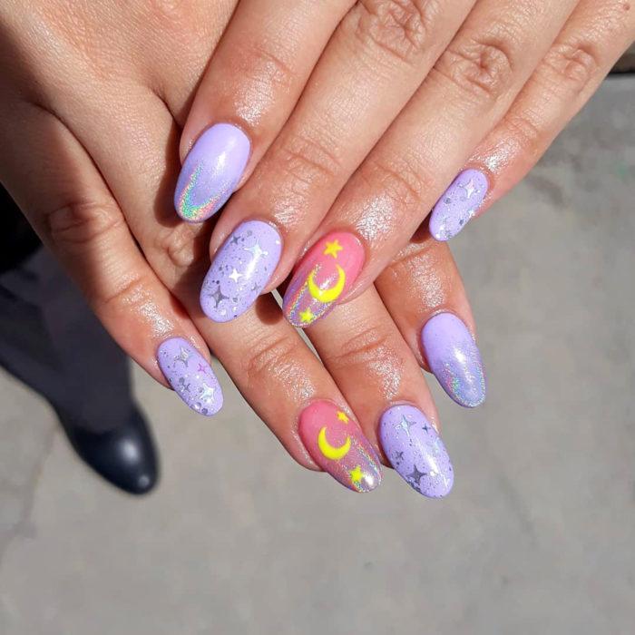 Manicura de Sailor Moon; uñas largas con forma de almendra pintadas de morado y rosa con lunas y estrellas