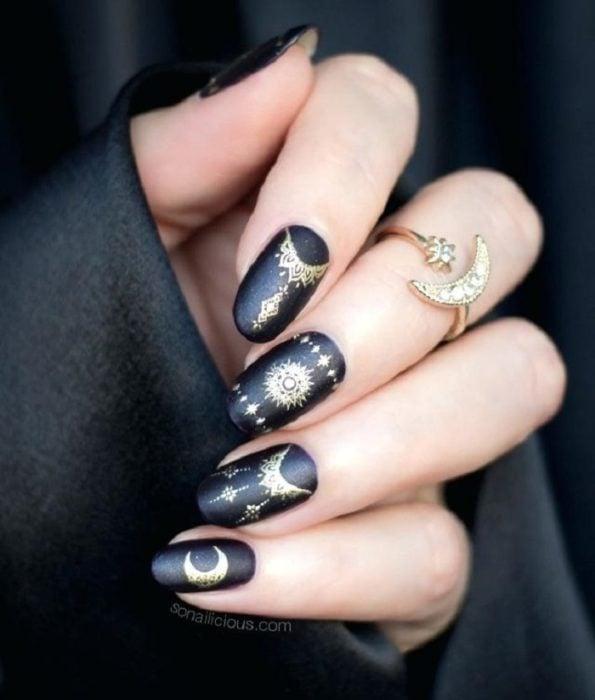 Uñas con manicura estilo bruja para Halloween; negras con detalles dorados