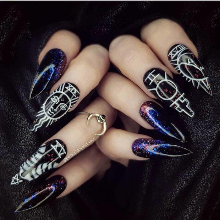 Uñas con manicura estilo bruja para Halloween; negras con detalles wiccas y azules con morado de galaxia; stiletto