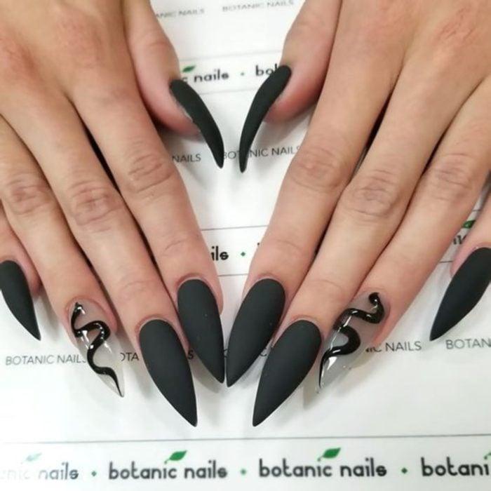 Uñas con manicura estilo bruja para Halloween; negras en forma de almendra con serpiente; stiletto