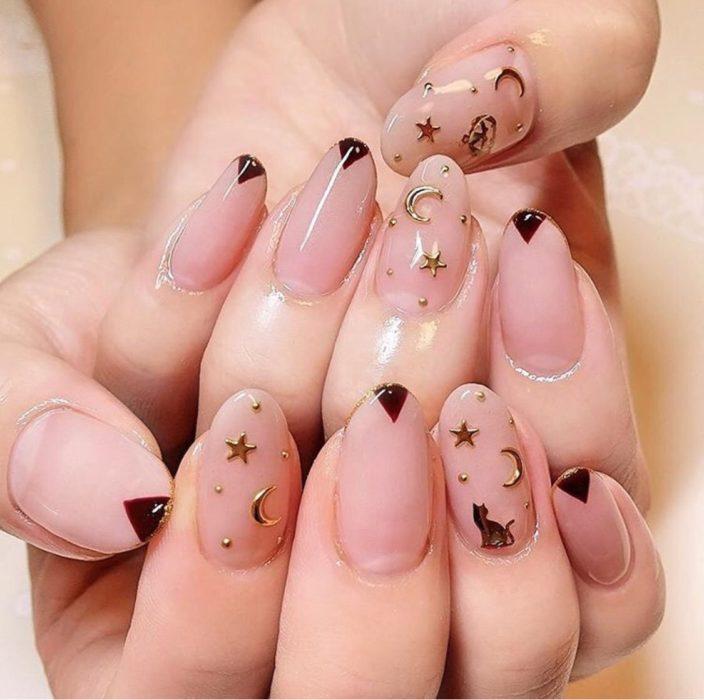 Uñas con manicura estilo bruja para Halloween; transparentes con lunas y estrellas doradas