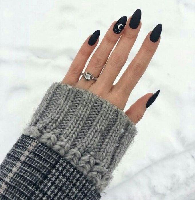 Uñas con manicura estilo bruja para Halloween; negras con una luna pequeña blanca; stiletto