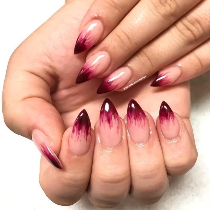 Uñas con manicura estilo bruja para Halloween; rojas y transparentes; stiletto