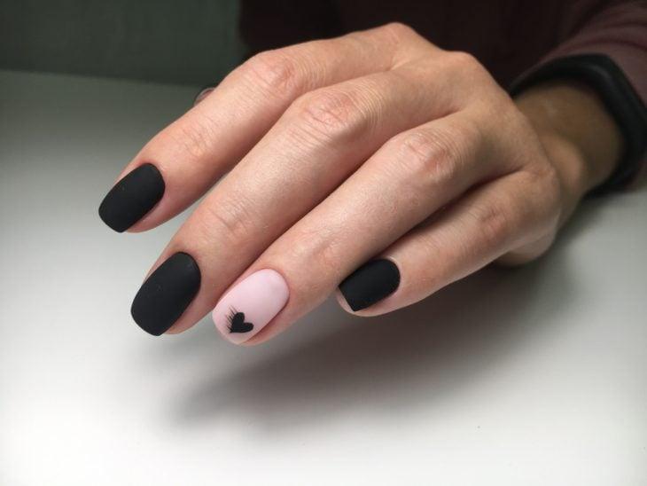Mano con uñas cortas en forma cuadrada de color negro mate con una uña de color rosa con diseño de corazón