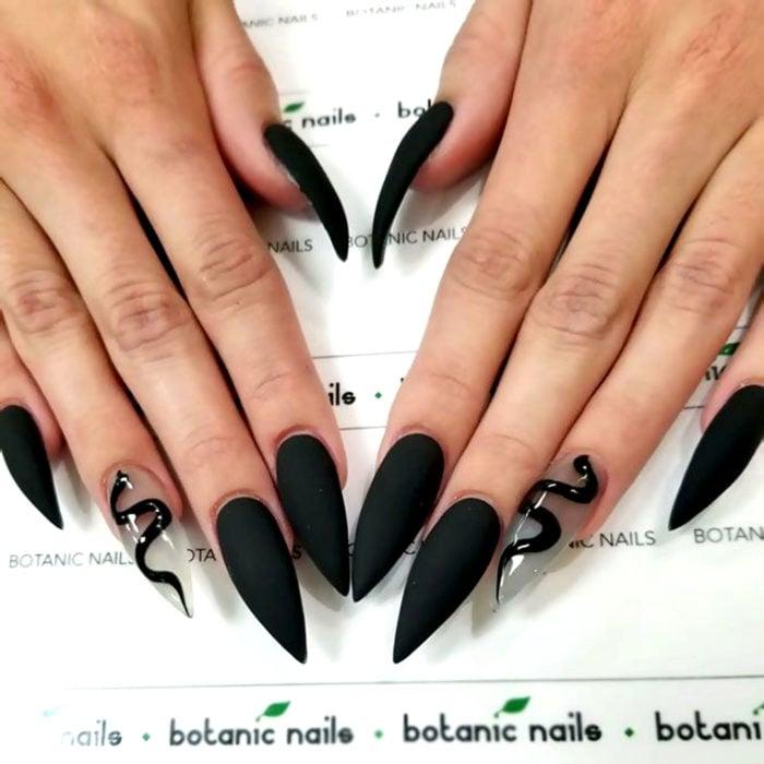 Uñas largas en forma stiletto, color negro mate con una uña transparente con dibujo de serpiente