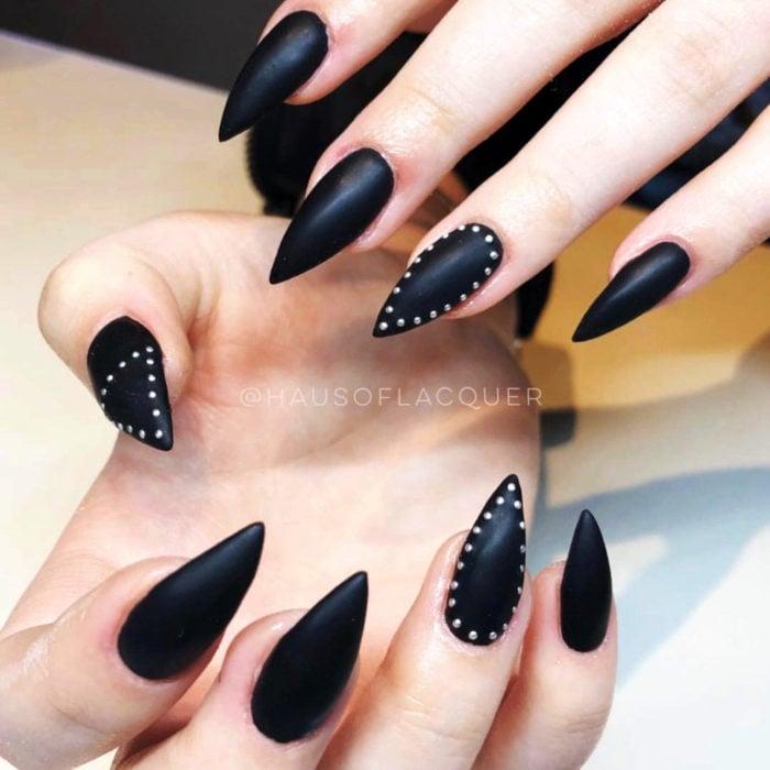 Uñas largas en forma de stiletto color negro mate con piedras que asemejan estoperoles