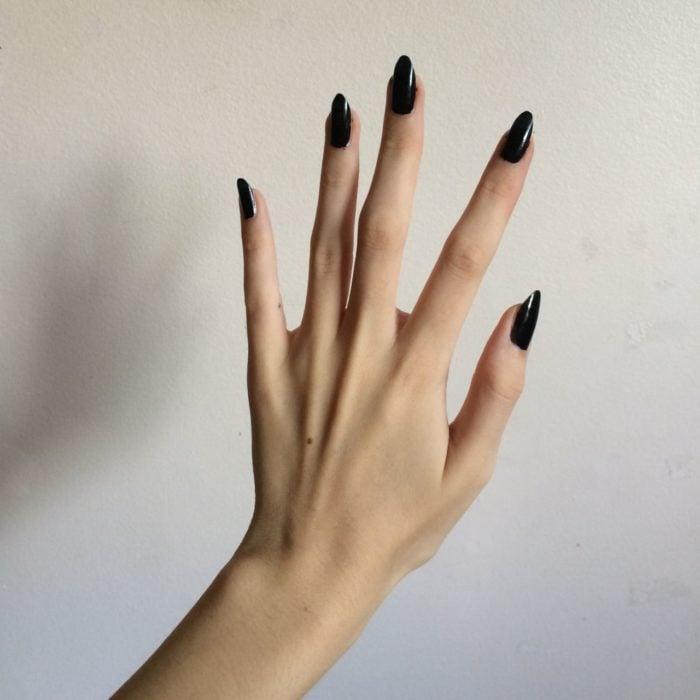 Mano de mujer delgada y larha con uñas largas stiletto color negro
