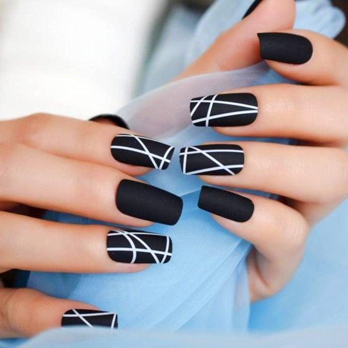 Uñas largas en forma cuadrada color negro mate con diseños de líneas blancas