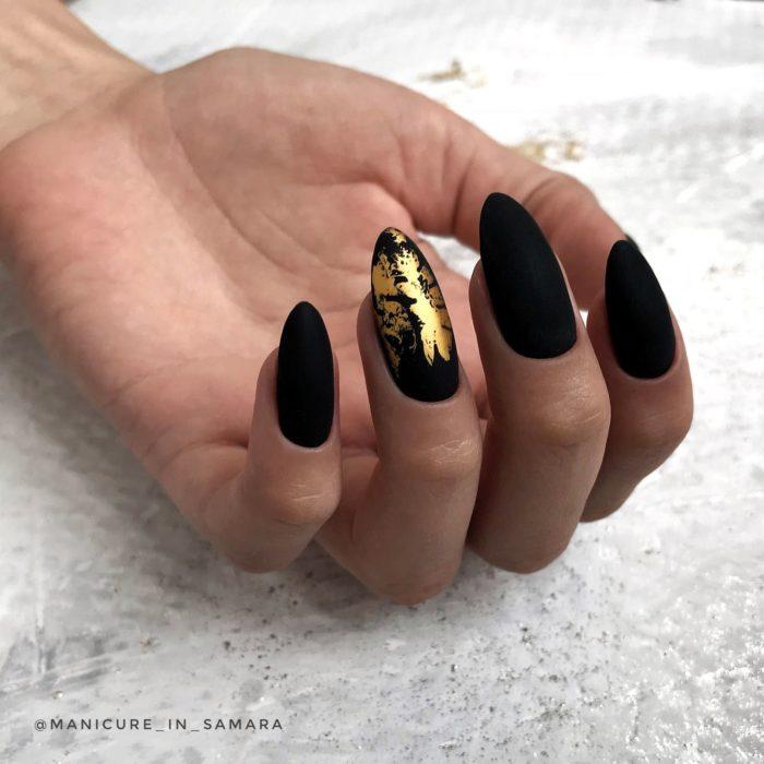 Uñas largas en forma de almendra color negro mate con una uña con detalles dorados