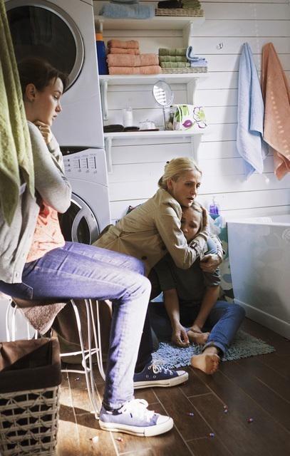 Una mujer abraza a una niña que está sentada en el piso de un cuarto de lavado, otra adolescente les mira sentada en un banco a un lado de ellas