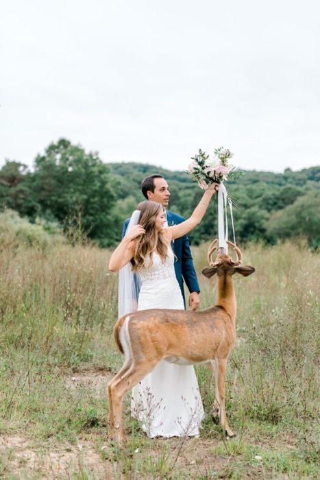 los novios suben el ramo mientras el ciervo se mantiene frente a ellos