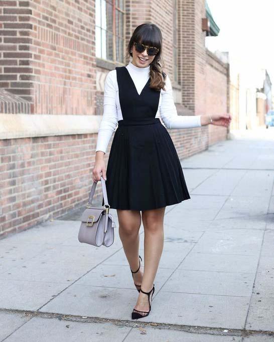 Chica caminando por la calle mientras usa un vestido pichi de color negro con una blusa blanca debajo de él