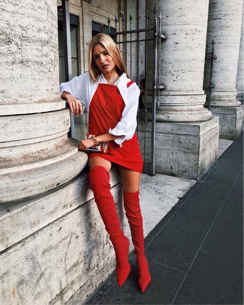 Chica recargada a un lado de una columna mientras usa un vestido pichi color rojas y botas arriba de la rodilla
