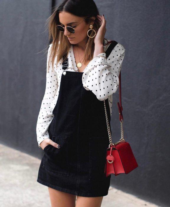 Chica usando un vestido pichi con una blusa de lunares debajo