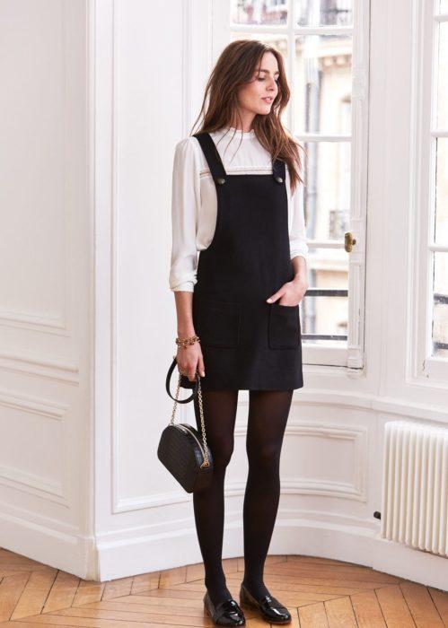 Chica usando un vestido pichi de color negro con una blusa blanca y unas medias negras