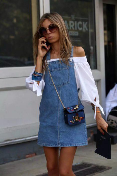 Chica usando un vestido pichi de mezclilla con una blusa blanca estilo campesino