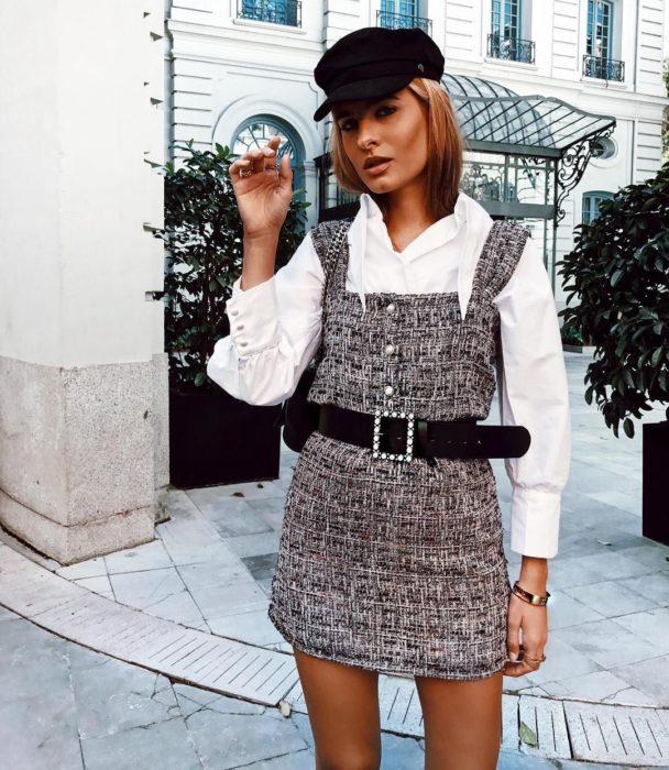 Chica usando un vestido pichi de lana con un cinturón y una boina de color negro