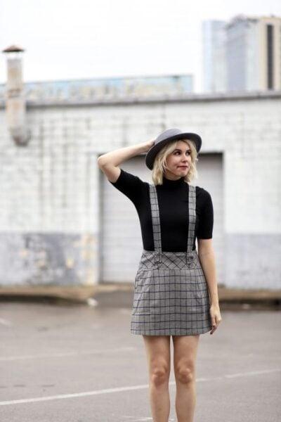 Chica usando un vestido pichi con estampado escoces de color gris