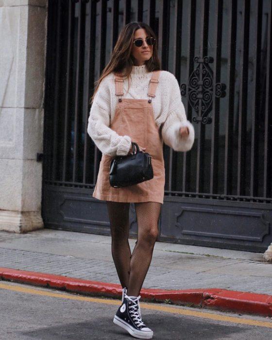 Chica usando un vestido pichi de color salmón con un suéter de color perla