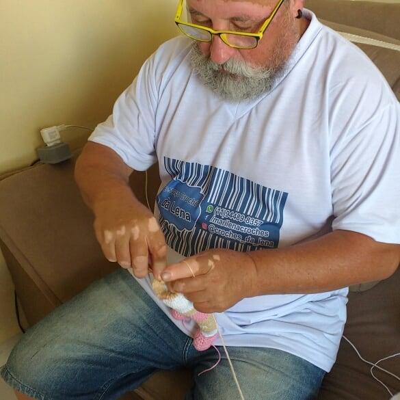 Joao Stanganelli tejiendo una muñeca, sentado en un sofá y usando lentes y una camiseta