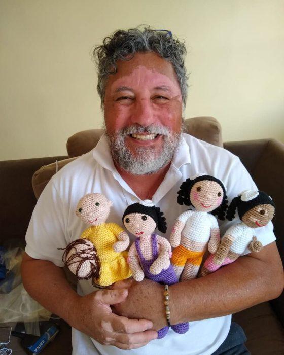 Joao Stanganelli sosteniendo a cuatro muñecas