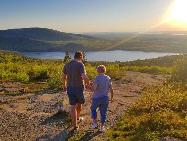 Brad y Joy caminan de la mano hacia un lago entre montañas