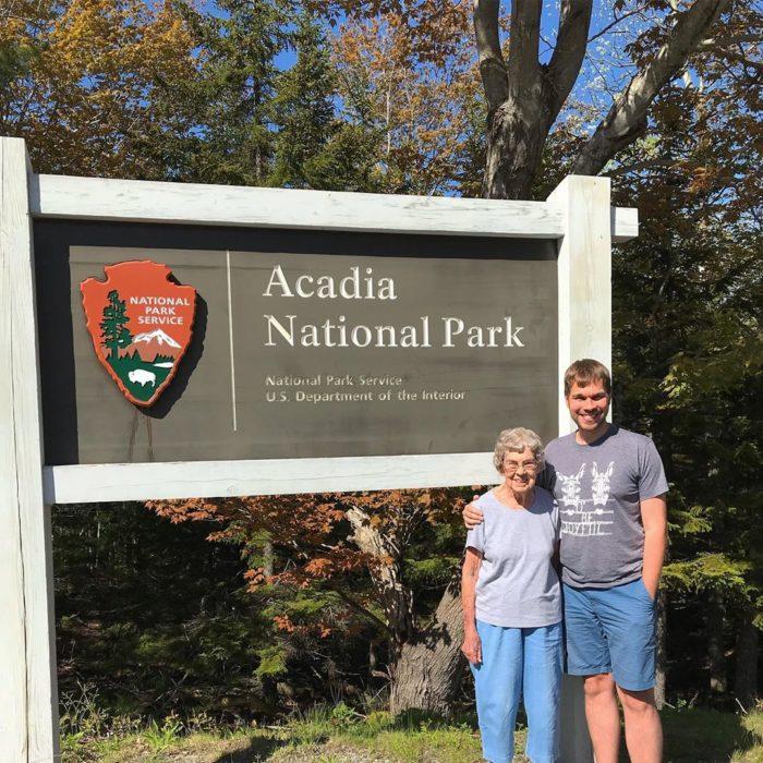 Brad y su abuela a un lado del letrero del Parque Nacional Acadia