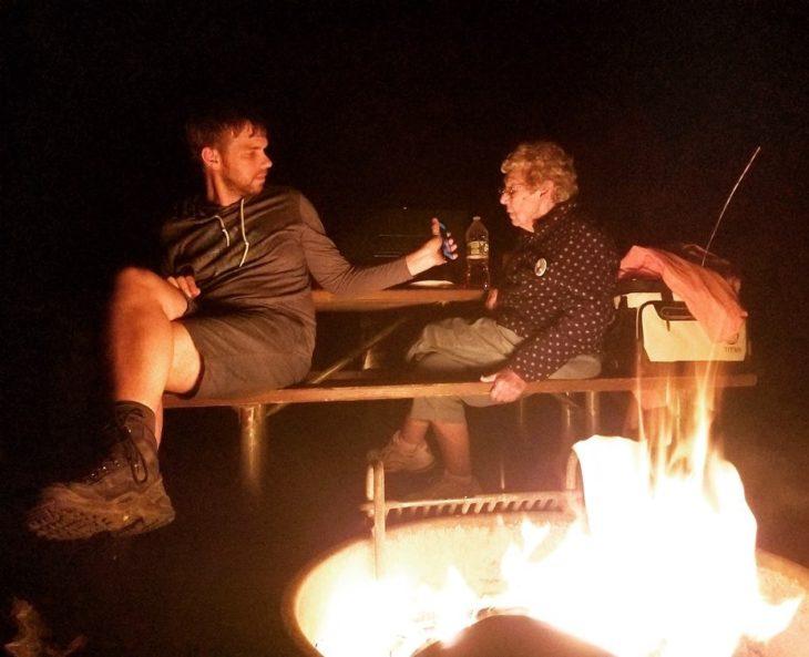 Brad y su abuela en la noche en un campamento, él le muestra algo en el teléfono