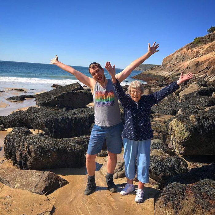 Joy y su nieto Brad en una playa con rocas con los brazos abiertos hacia arriba