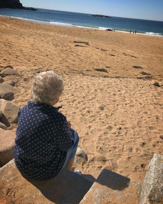 Joy, la abuela de Brad sentada en la playa viendo hacia el mar