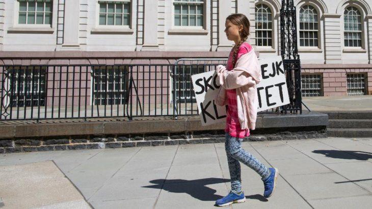 Greta Thunberg camina por una acera con un cartel bajo el brazo y un edificio de fondo