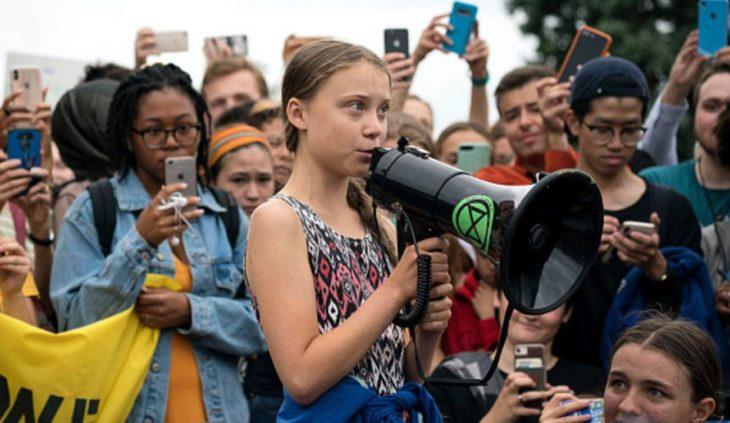 Greta Thunberg habla por un altavoz rodeada de jóvenes
