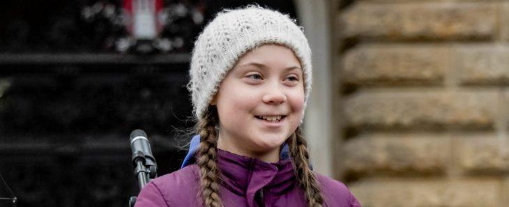 Greta Thunberg con un gorro beige tejido, sonriente