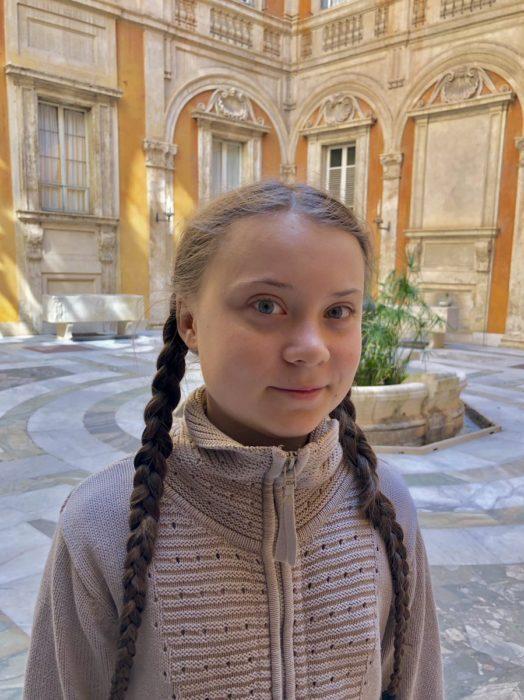Greta Thunberg en un patio interior de un edificio con chamarra café y sus trenzas