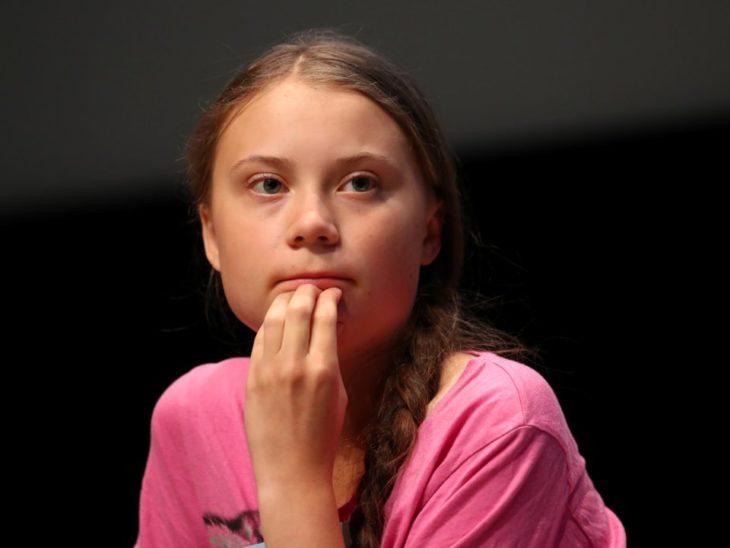 Greta Thunberg recargada sobre su brazo pensativa
