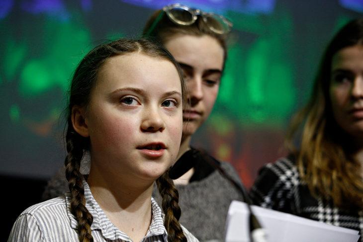 Greta Thunberg lee de una hoja frente a un micrófono, con camisa de cuadros